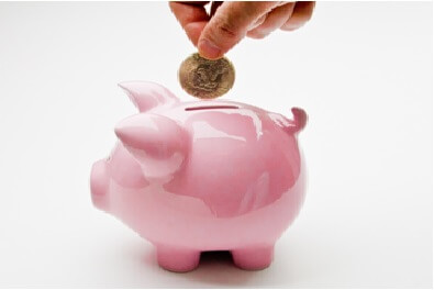 single coin being inserted into a piggy bank