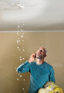 man with phone and yellow pages in-hand trying to resolve a leak from the flat above