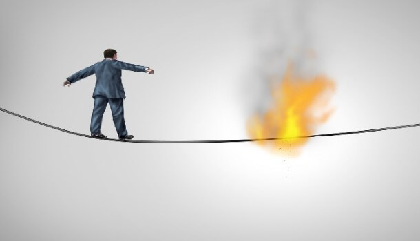 A man walking a tightrope with the rope on fire in the middle.