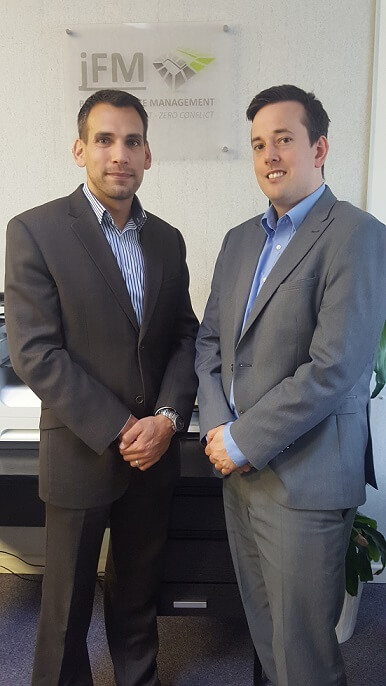 Photo of the owners of JFM, James Farrar & Joe Mallon standing in front of a picture of their company's logo